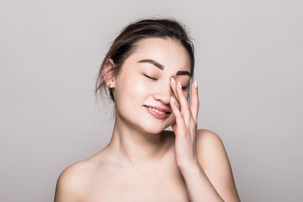 アジアの女性の美しさの顔のクローズアップの肖像画。灰色の壁に分離された完璧な肌を持つ美しい魅力的な混血アジア女性モデル