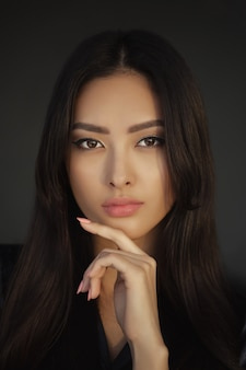 アジアの女性の美しさの顔のクローズアップの肖像画。屋内でポーズをとって黒いドレスの美しい少女