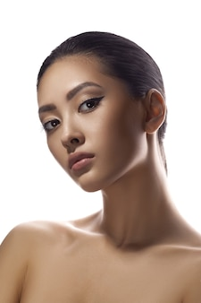 Asian woman beauty face closeup portrait beautiful young girl with bare shoulders posing indoors