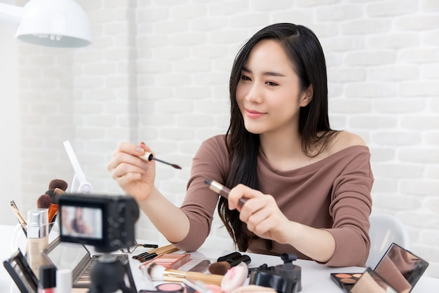 Asian woman beauty vlogger doing cosmetic makeup tutorial video