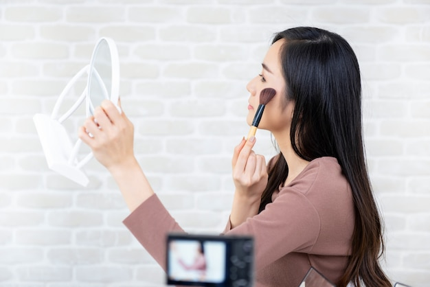 Asian woman beauty vlogger recording makeup tutorial for viral clips