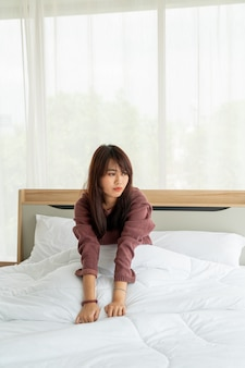 Asian woman on bed and waking up in the morning