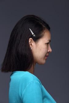 Азиатская женщина перед нанесением составляет черную прическу синюю рубашку. без ретуши, свежее лицо с прыщами, красивая и гладкая кожа. студийное освещение серый фон, вид сзади сбоку сзади