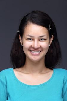 Азиатская женщина перед нанесением составляет черную прическу синюю рубашку. без ретуши, свежее лицо с прыщами, красивая и гладкая кожа. студия освещения серый фон