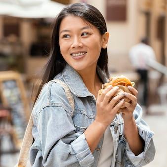 Азиатская женщина счастлива после покупки уличной еды