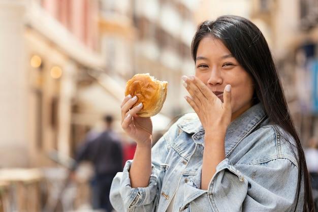 屋台の食べ物を買って幸せなアジアの女性