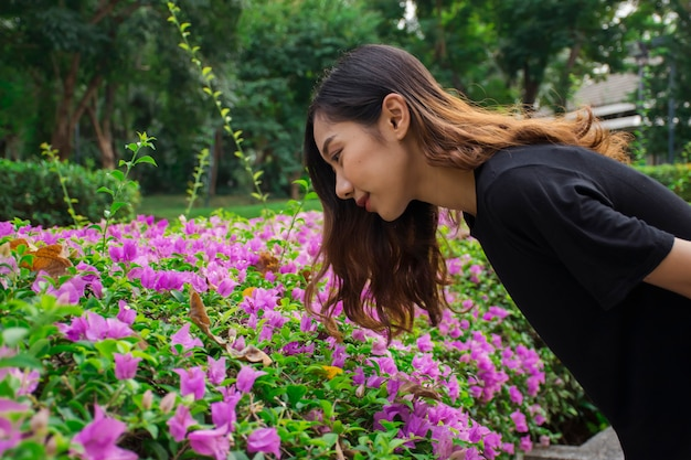 Asian woman bent down to look at the purple flowers (bougainvillea) with public park