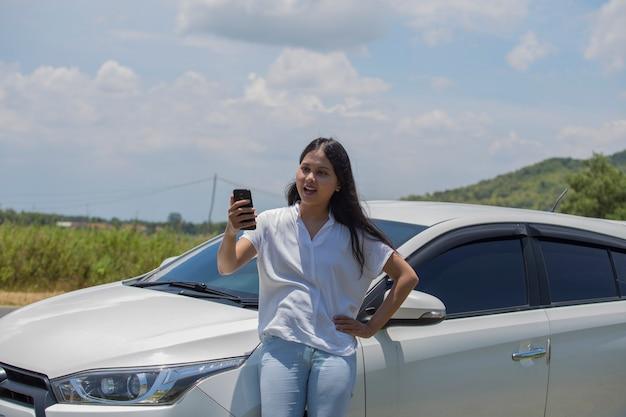 Asian woman beside a car using smart phone