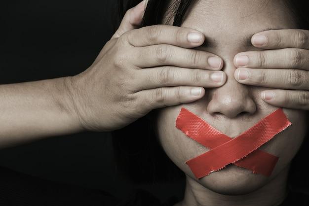 Азиатская женщина с завязанными глазами заворачивает рот красной липкой лентой