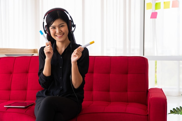 헤드폰으로 소파에 앉아 두 개의 펜을 들고 아시아 여성 블로거 인플 루 언서