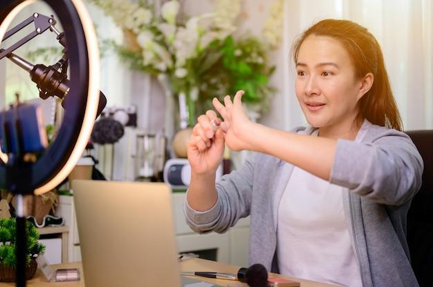 Азиатская женщина-блогер или видеоблогер, работающая в интернете по вопросам красоты и макияжа. образ жизни влиятельного лица в социальных сетях и создателя контента дома.
