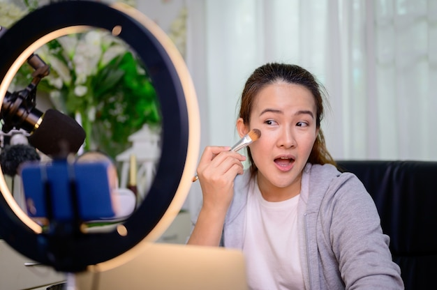 Азиатская женщина-блогер или видеоблогер, работающая в интернете по вопросам красоты и макияжа. образ жизни лидера мнений в социальных сетях и создателя контента дома.