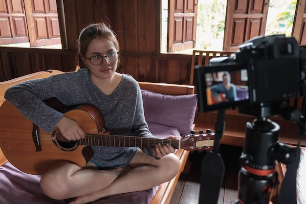 Asian woman blogger playing guitar on social media. concept of guitarist online lesson while stay at home
