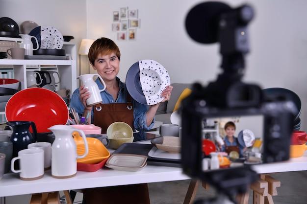 Азиатская женщина-блогер, влогер и онлайн-авторитет, записывающая видеоконтент по интернет-маркетингу и продажам, а также электронной коммерции для изготовления керамических изделий и изделий из нее.