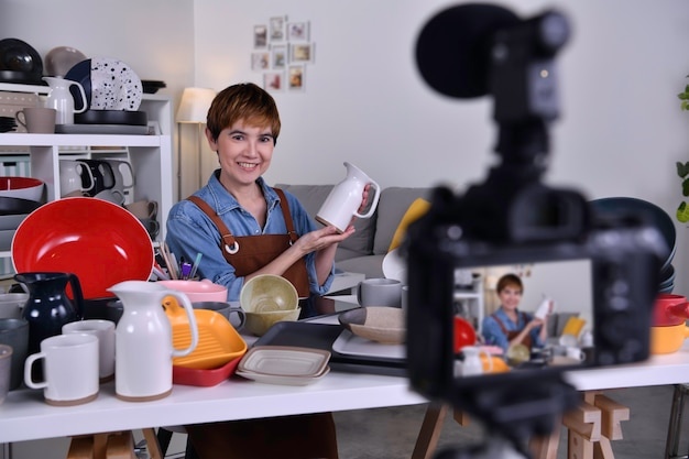 Asian woman blogger vlogger and online influencer recording video content on online marketing and selling and e-commerce for ceramic making and products