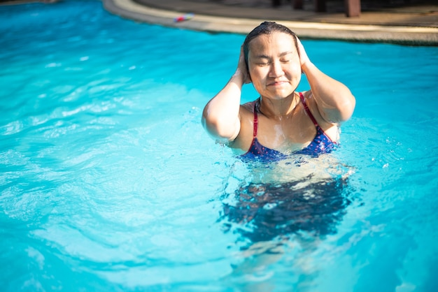 Asian woman in a blue bikini  swims in the pool , summer vacation