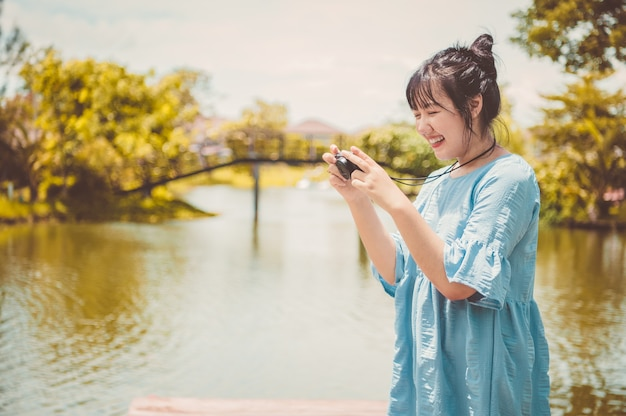 Asian woman in blue dress in public park carrying digital mirrorless camera and taking photo without facial mask in happy mood. people lifestyle and leisure concept. outdoor travel and nature theme.