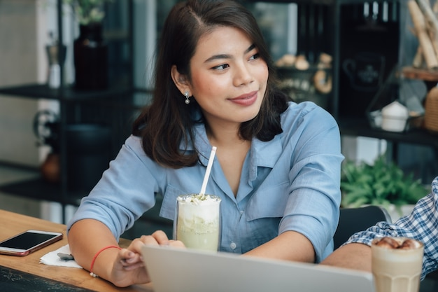 Asian woman in blue shirt  in cafe drinking coffee and talking with boy friend smile and happy face