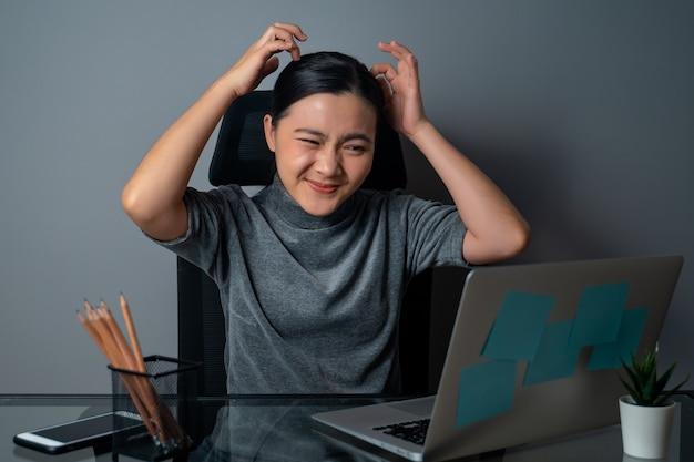 아시아 여자는 지루하고 짜증이 나고, 그녀의 머리를 긁적이며, 사무실에서 랩톱에서 작업합니다.