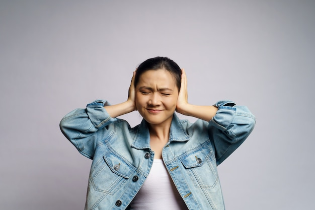 Asian woman bored and annoyed, covering her ears isolated.
