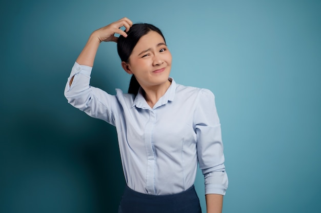 Asian woman bored and annoyed, scratching her head, isolated on blue.