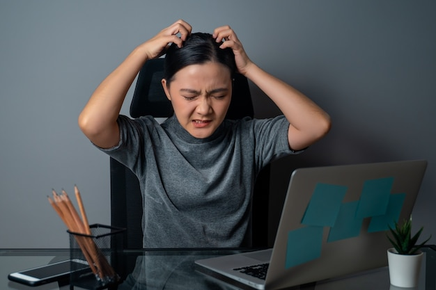 Asian woman bored and annoyed, scratching her head, working on a laptop at office