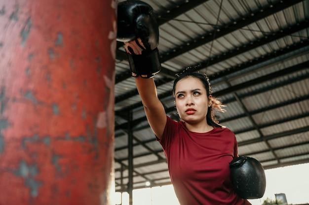 훈련 캠프에서 샌드백을 치는 아시아 여자 복서 시험 운동