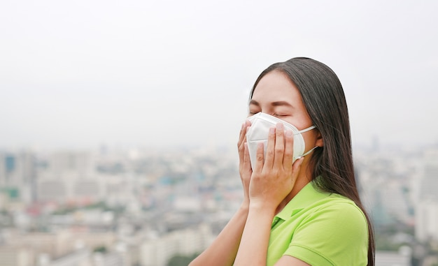 Asian woman breathing by wearing a protection mask against air pollution in bangkok city.