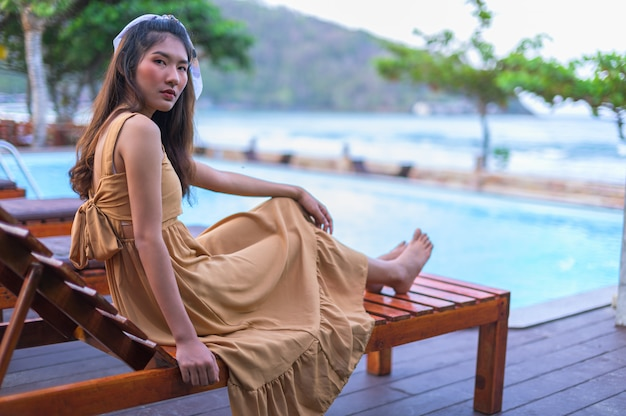 Asian woman in a brown dress relax feel happy. with tourism at the pool