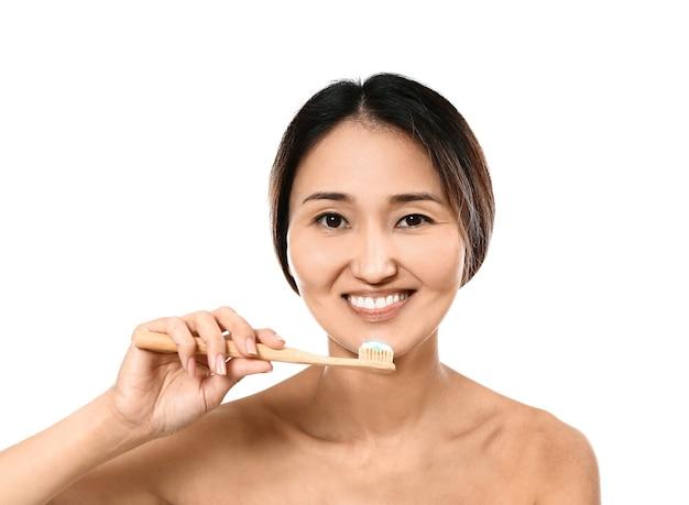 Азиатская женщина, чистящая зубы на белом