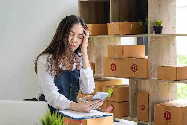 スマートフォンを持っているアジアの女性ビジネスオーナーは、自宅で小包ボックスを注文することで頭痛を強調します。