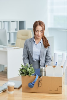 Asian woman in business suit standing in office with belongings in cardboard box on desk