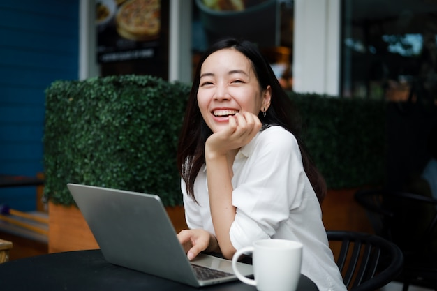 Asian woman at a cafe working on a laptop