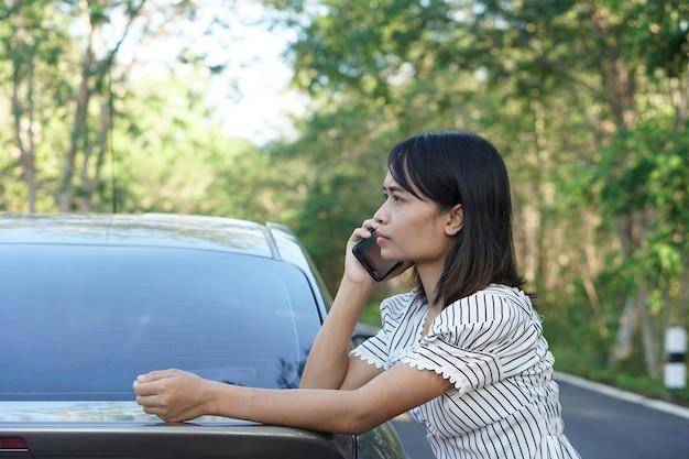 アジアの女性整備士に電話すると、車は森の周りの道路に出かけます。