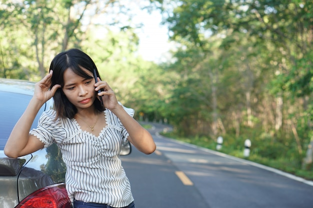 Asian woman call a mechanic, the car goes out on the road around the forest.