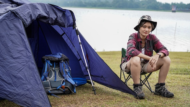 Asian woman camping at reservoir and sit down in chair