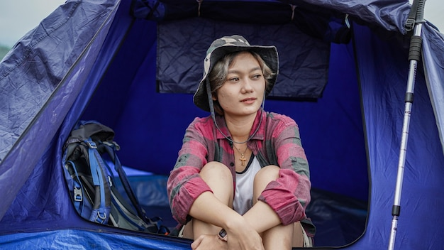 Asian woman camping at reservoir and sit down in tent