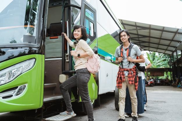문 손잡이를 잡고 배낭과 헤드폰을 들고 아시아 여자는 버스에 타기 위해 줄을 서서 승객의 벽과 함께 버스에 도착