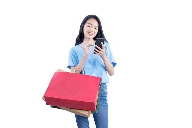 白い壁に隔離された携帯電話を保持している買い物袋を運ぶアジアの女性