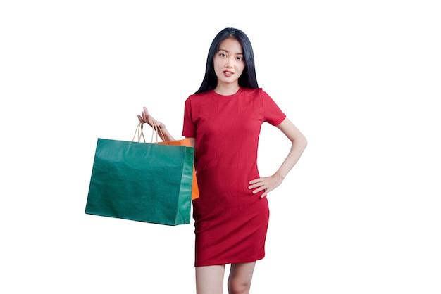 白い背景で隔離の買い物袋を運ぶアジアの女性
