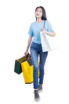 白い壁に隔離された買い物袋を運ぶアジアの女性