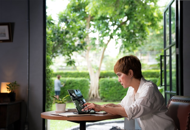 Asian woman in casual clothing using laptop working indoors at home