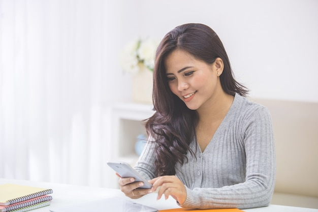 Asian woman in casual using mobile phone
