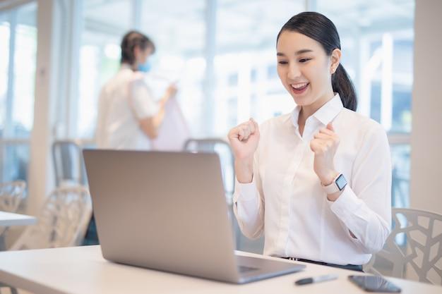 아시아 여자는 노트북, 성공 행복 포즈와 함께 축 하합니다.