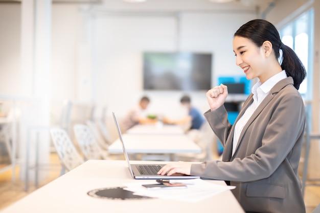 아시아 여자는 노트북, 성공 행복 포즈와 함께 축 하합니다. 프리미엄 사진
