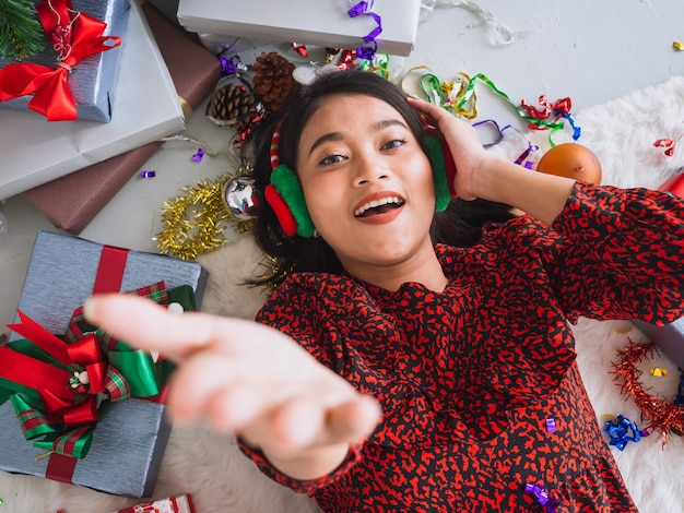 Asian woman celebrating new year and christmas on floor with gift box