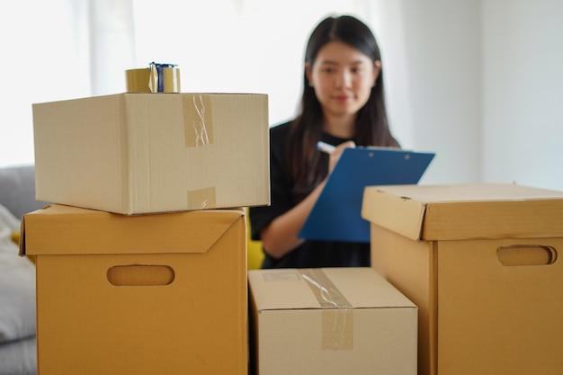 カートンボックスをチェックして梱包するアジアの女性は、ぼかしの動きのあるチェックリストで新しい家に移動する準備をします。