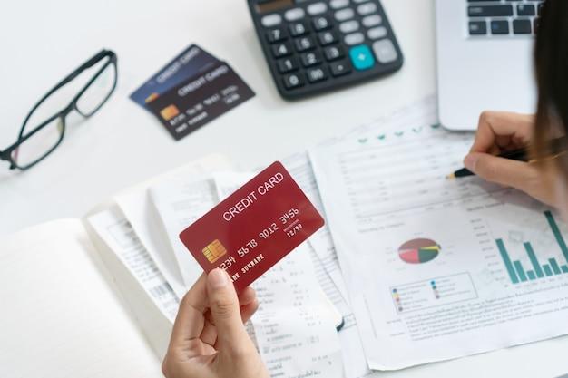 手形、税金、銀行口座の残高をチェックし、クレジットカードの費用を計算するアジアの女性。家族の予算と財政の概念。上面図