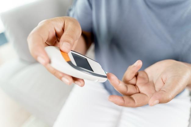 Азиатская женщина проверяет уровень сахара в крови с помощью цифрового глюкометра, здравоохранения и медицины, диабета, концепции гликемии