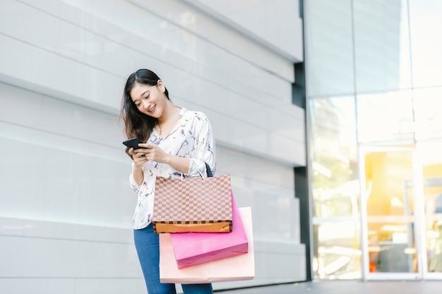 Asian woman checking smart phone and smile with shopping bags enjoy in shopping mall